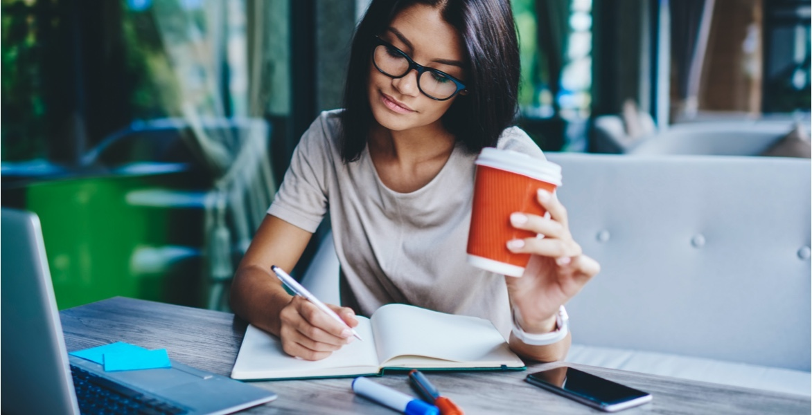 A woman taking notes while holding a mug